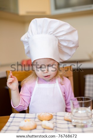 Little girl ready to eat cakes on kitchen