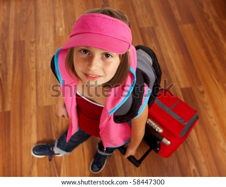 Little girl ready to travel, carrying red luggage - stock photo