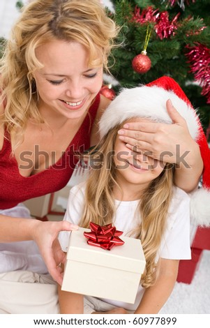 Little girl receiving surprise christmas present from her mother - stock photo