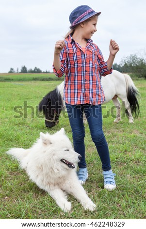 Little girl rejoices while standing on green grass with white dog and pony on farm