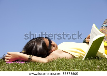 little girl relaxing at the top of the field reading a book - stock photo