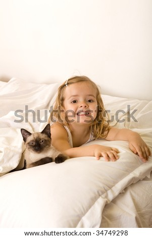 Little girl relaxing on the bed with her kitten - stock photo