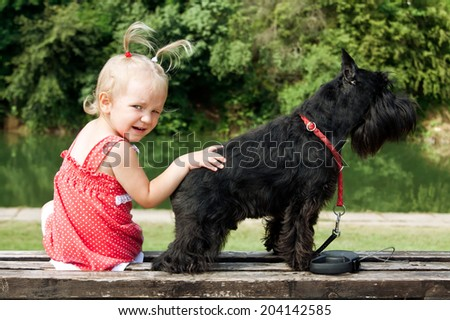 little girl relaxing outside with her dog