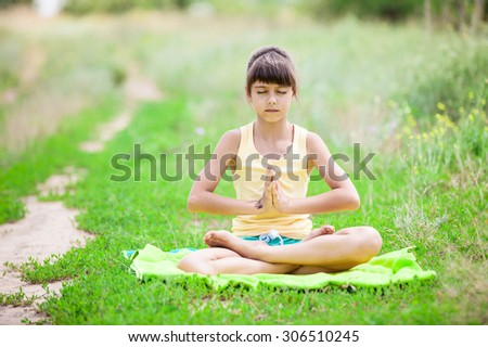 Little girl relaxing while sitting in lotus positionon on grass. - stock photo