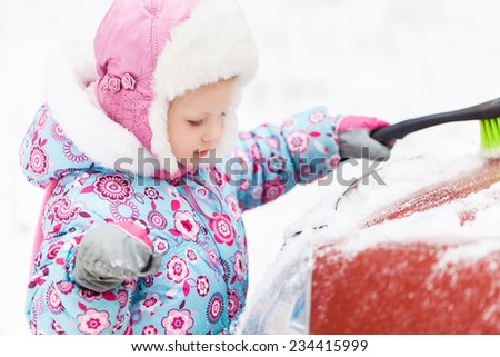 Little Girl removing snow from car - stock photo