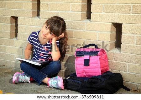 Little girl resting after a long day at school - stock photo