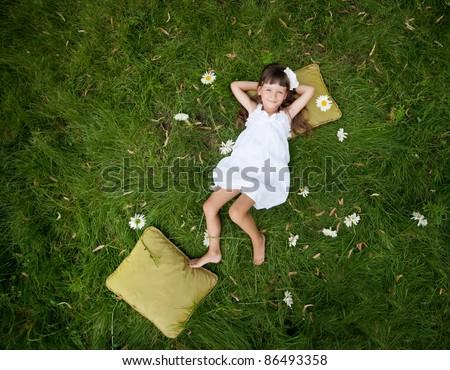 little girl resting on soft pillow in fresh spring grass - stock photo