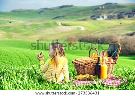 Little girl reversed back doing a picnic in the countryside of Tuscany. - stock photo