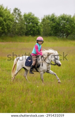 Little girl rides a beautiful horse and smiling - stock photo