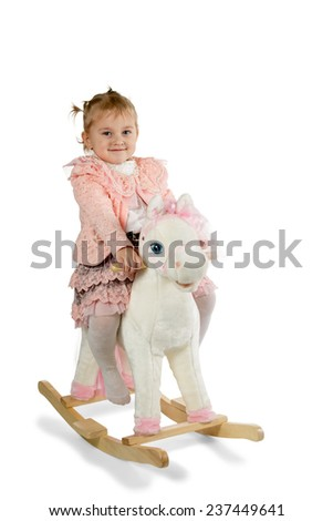 Little girl rides a toy horse rocking isolated on a white background - stock photo