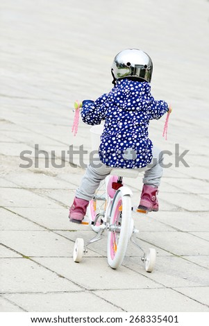 Little girl riding a bicycle in spring - stock photo