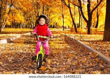 Little girl riding a bicycle in the park on the road covered with autumn oak and maple trees - stock photo
