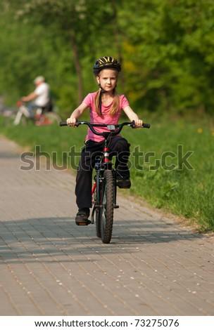 Little girl riding a bike - stock photo