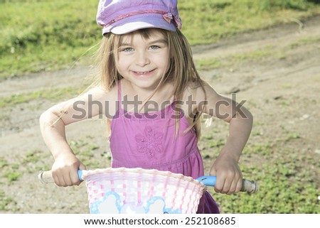 Little girl riding a bike on the country road. - stock photo