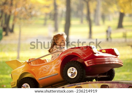 Little Girl Riding a Car In Amusement Park Outdoor