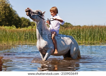 Little girl riding a horse in a river - stock photo
