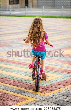 little girl riding bicycle in city park. - stock photo