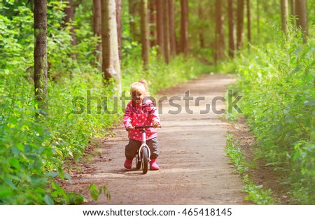 little girl riding bike in summer forest