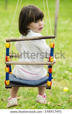 little girl riding on a swing on a green background - stock photo