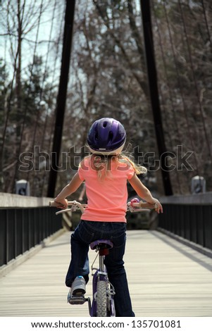 Little girl riding on her bicycle - stock photo