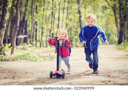 little girl riding scooter and boy running, active kids sport - stock photo