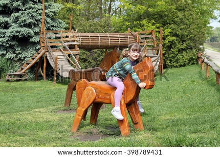 little girl riding wooden horse on playground - stock photo