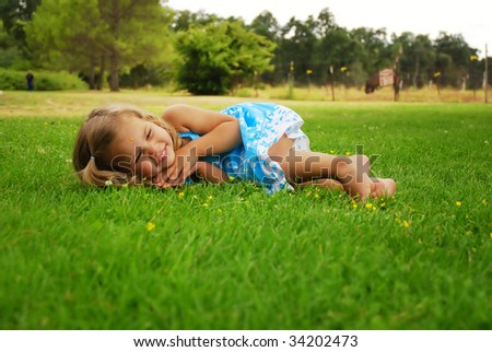 Little girl rolling around in grass at a horse farm - stock photo