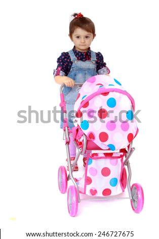 Little girl rolls the stroller.concept childhood education and child development.Isolated on white background - stock photo
