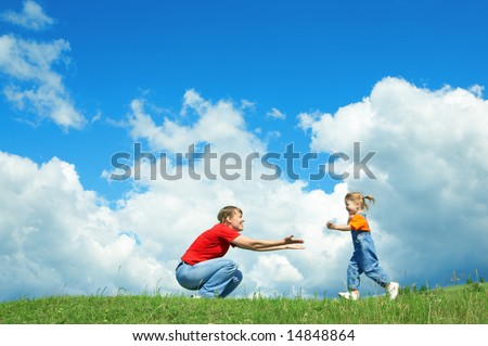 little girl run to mother embrace on green grass under sky with clouds - stock photo