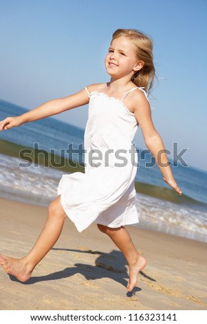 Little Girl Running Along Beach - stock photo