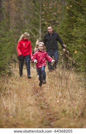 Little girl running in front of her family - stock photo