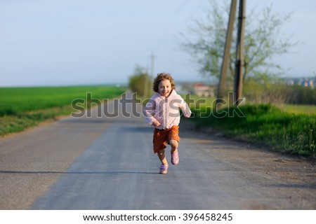 Little girl running on a meadow in a field. Happy child, kid playing and having fun outdoors in summer. - stock photo
