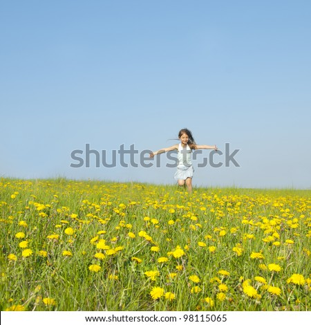 Little girl running on a meadow in a field of flowers, dandelions - stock photo