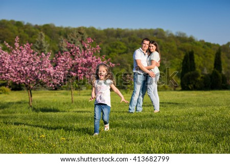 Little girl running on the green grass, parents hugging on the background. Happy family together - stock photo