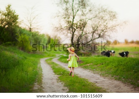 Little girl running on the road. Nature background with cows. - stock photo