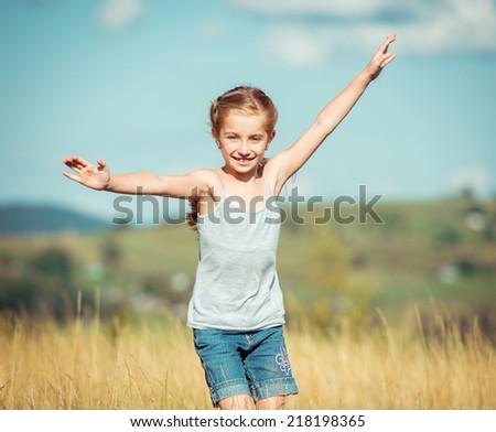little girl runs through a beautiful meadow - stock photo