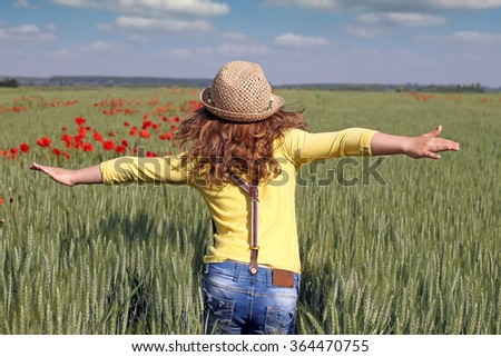 little girl runs through a field of green wheat