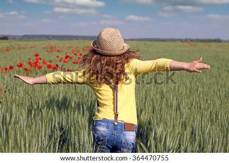 little girl runs through a field of green wheat - stock photo