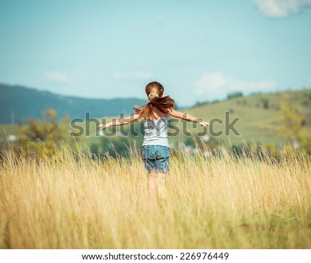 little girl runs through a  meadow in the mountains. back view - stock photo