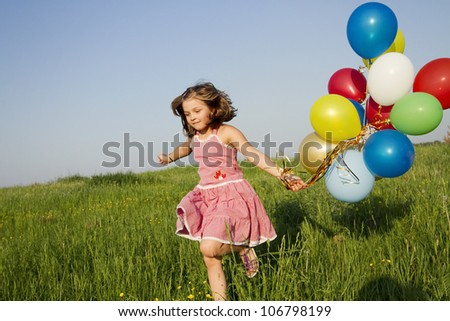 little girl runs with multicolored balloons - stock photo