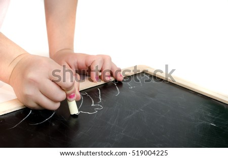 Little girl's hands writing on a small blackboard with a yellow piece of chalk isolated on white background