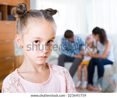 Little girl sad because of jealous younger sister to parents. focus on girl - stock photo