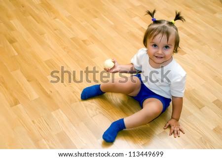 little girl sat on the floor with peeled apple - stock photo