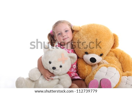 Little girl sat with cuddly toys - stock photo
