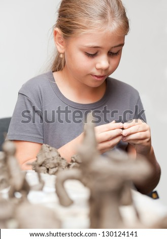 Little girl sculpts toy from clay with enthusiasm - stock photo