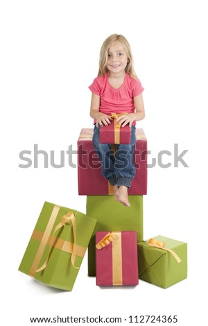 little girl seated on a stack of birthday presents, on white background - stock photo