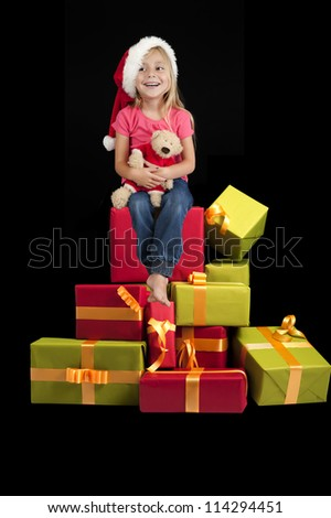 little girl seated on a stack of christmas presents, isolated on black background - stock photo