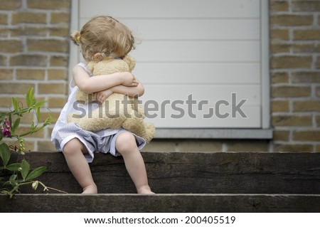 little girl seated on old wooden stairs with teddy bear - stock photo