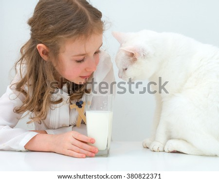 Little girl share glass of milk with cat. - stock photo