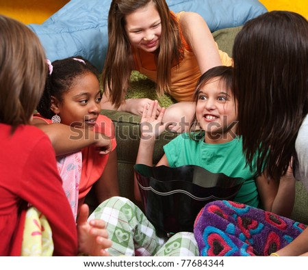 Little girl sharing a joke with her friends - stock photo